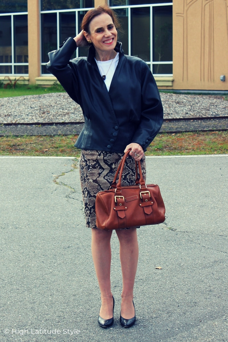 woman in fall outfit with trendy skirt, leather jacket, pumps, satchel