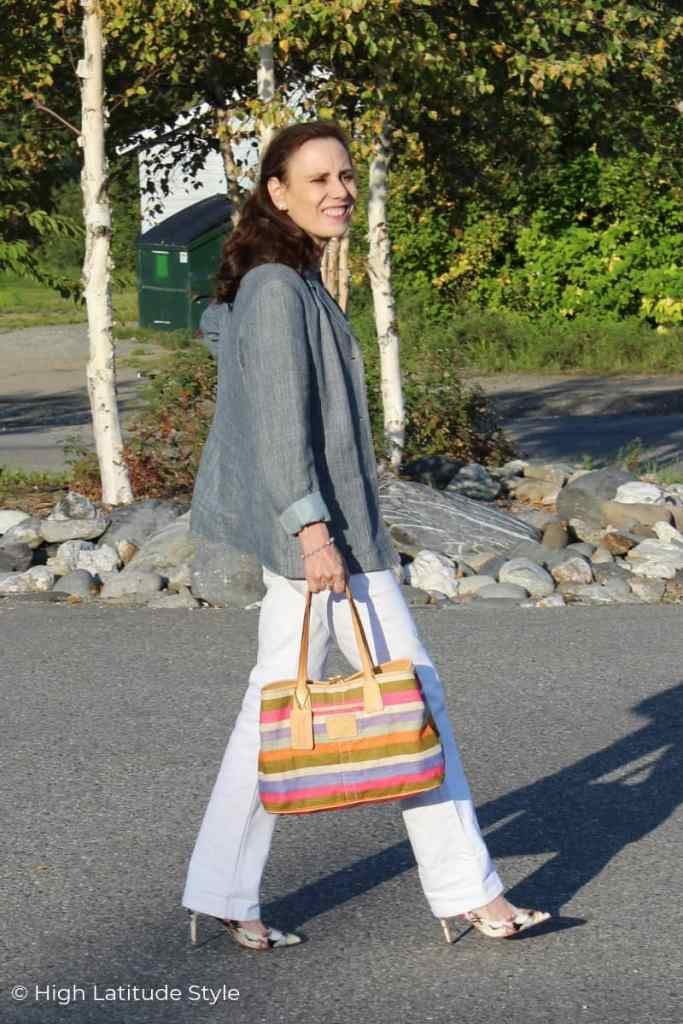 midlife woman in all neutrals pants and blazer outfit with colorful bag