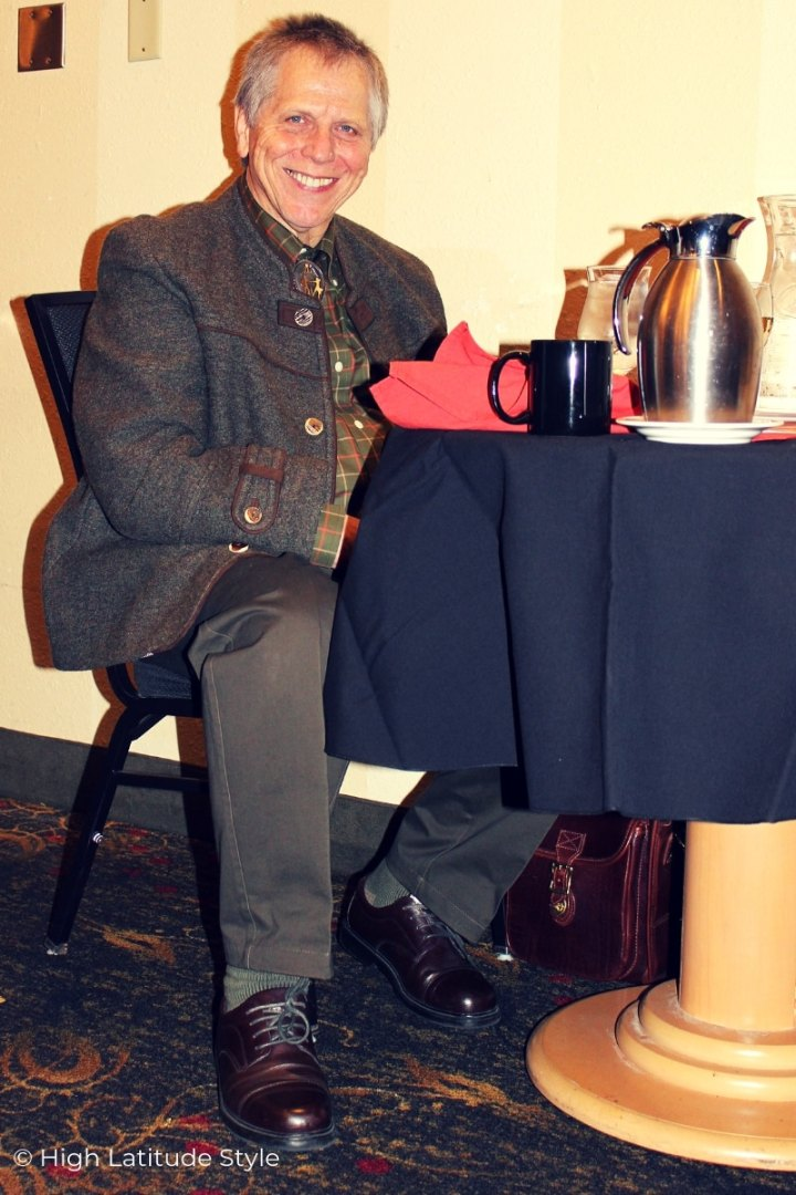 man in casual janker, wool pants sitting at a table