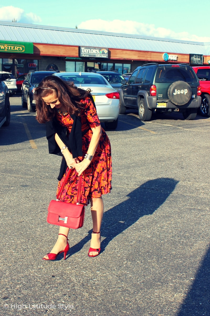 style blogger looking at her red sandals and bag