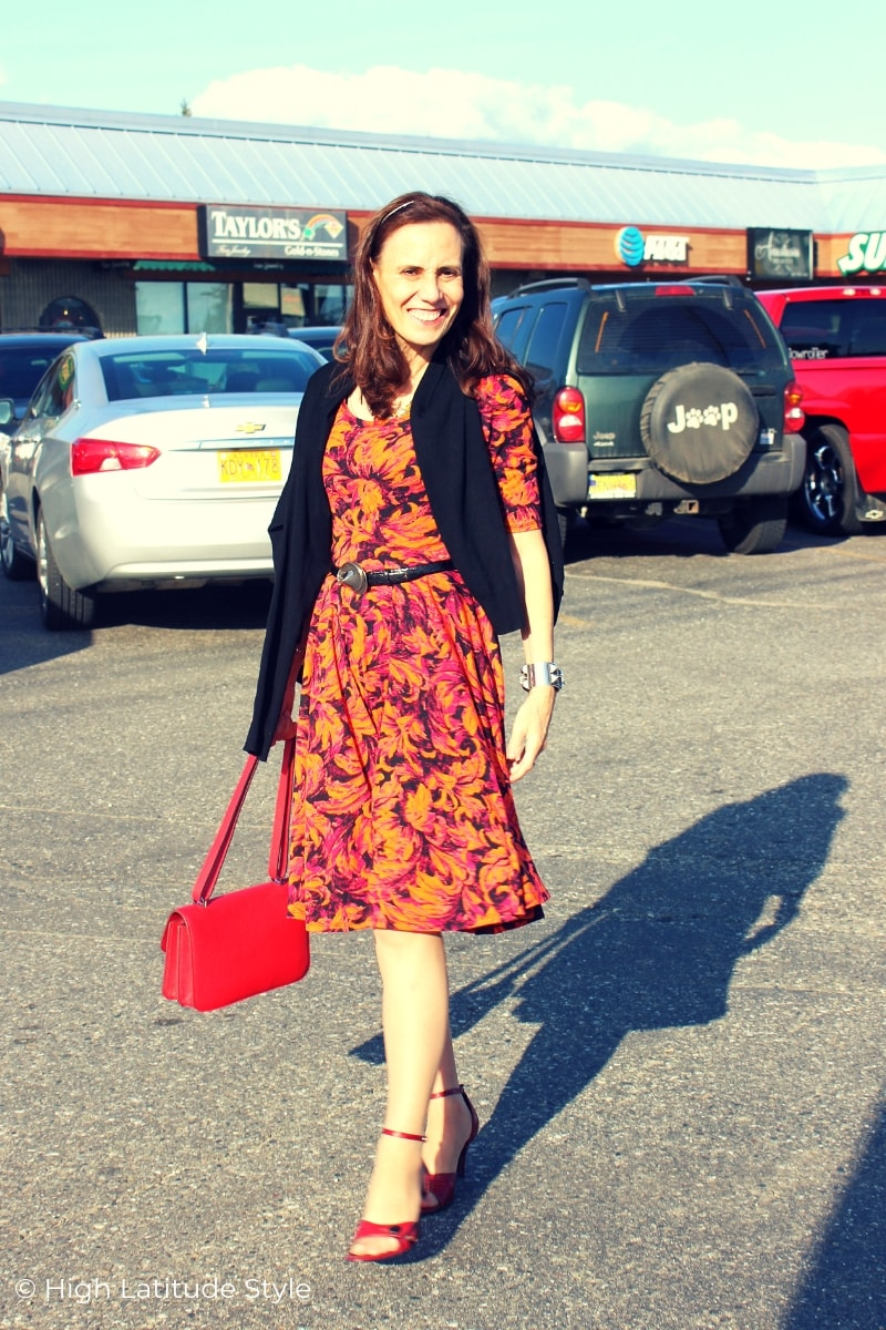 over 50 years old woman in orange, purple red dress with black cardigan and red heels