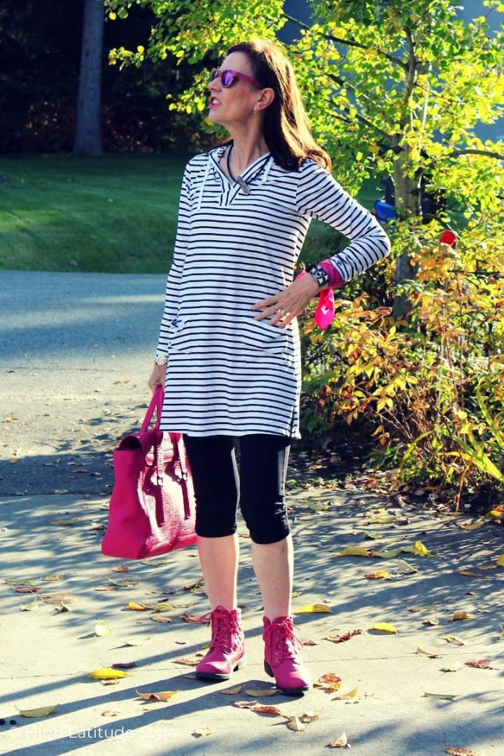 midlife woman looking posh in a black and white dress and leggings outfit with pop of pink
