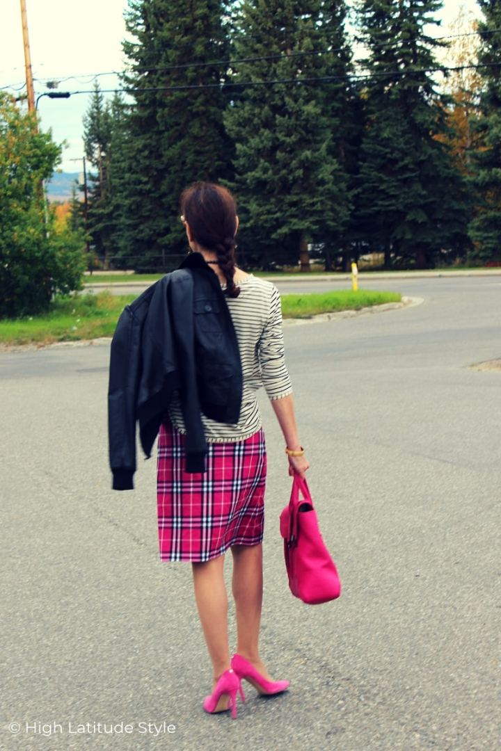 woman walking in tartan A-line skirt, bomber leather jacket and sweater