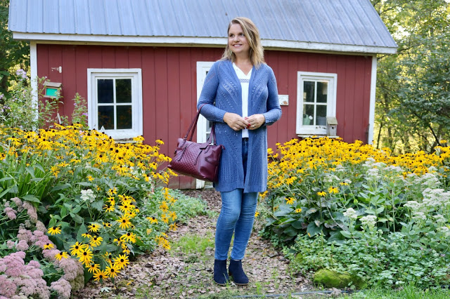 Top of the World OOTD Readers' Fav Amy in long blue knit cardigan and jeans in front of a house with flowers