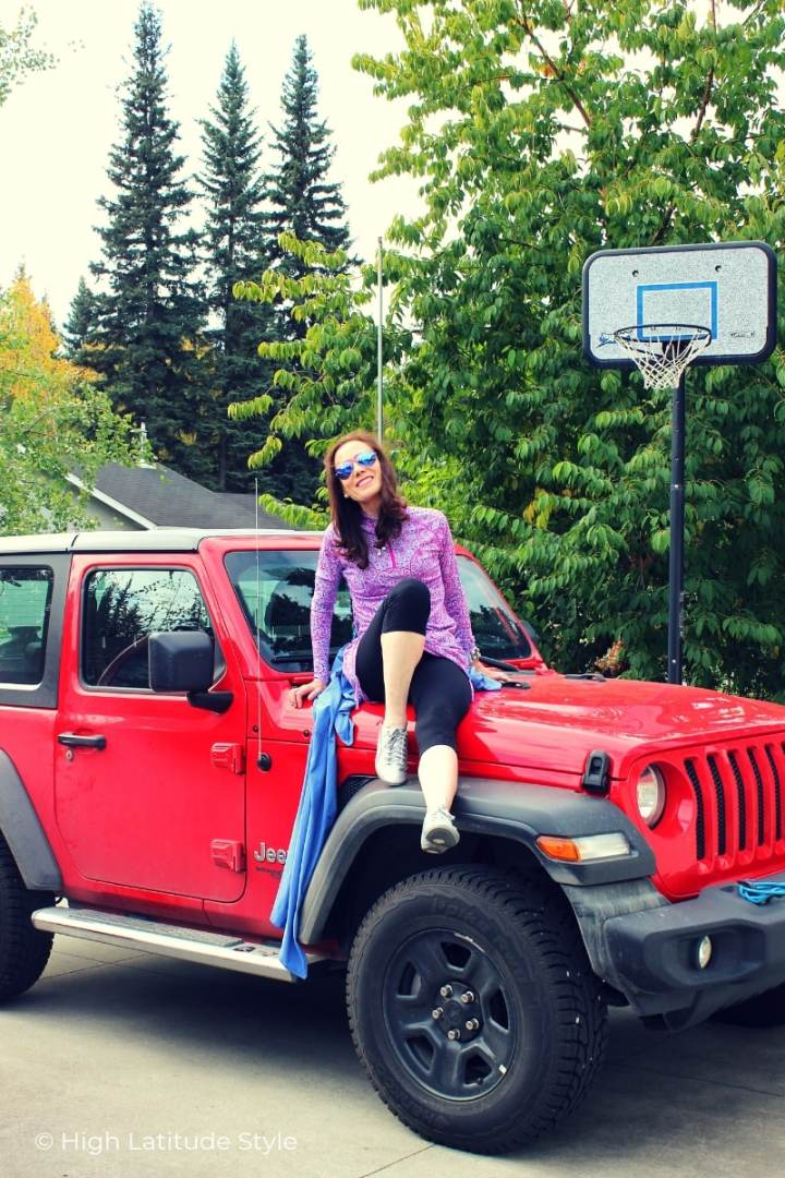 fashion blogger sitting on a Wrangler in swim capris, shirt, sneakers holding a beach shawl
