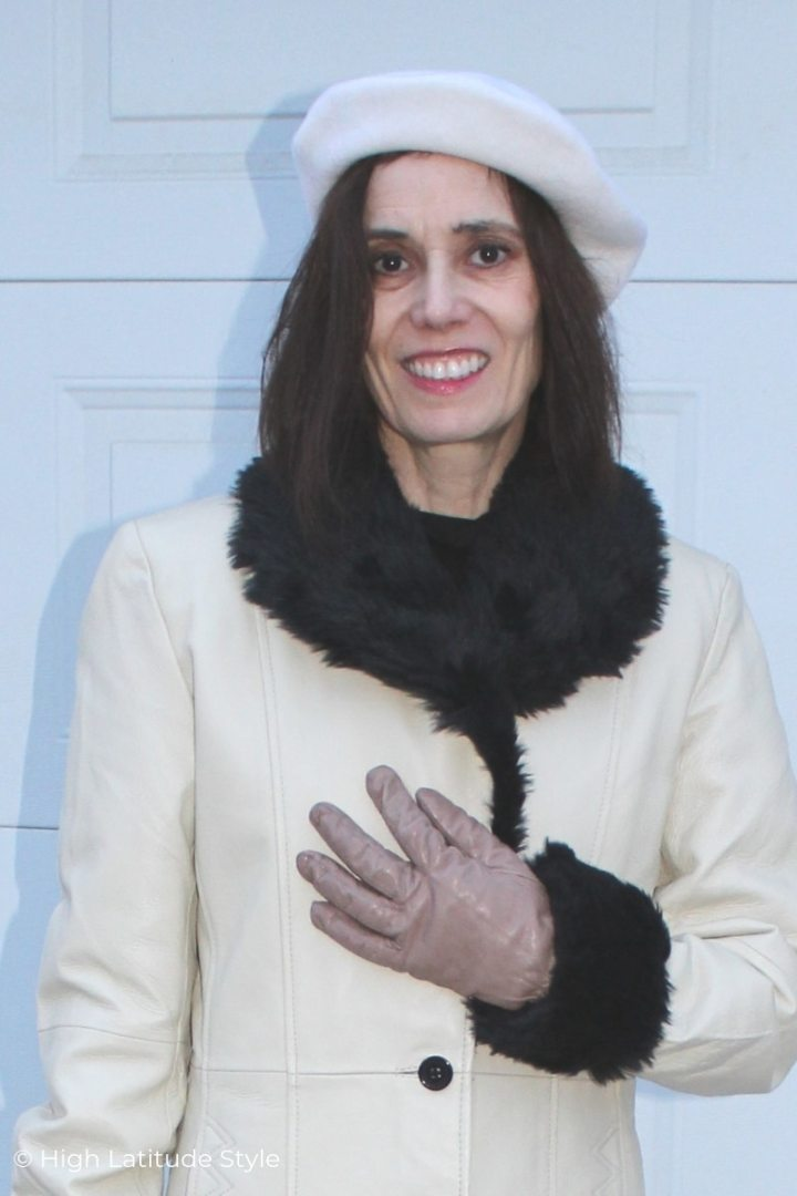 style book author in black and white winter style with coat with beret, gloves and turtleneck
