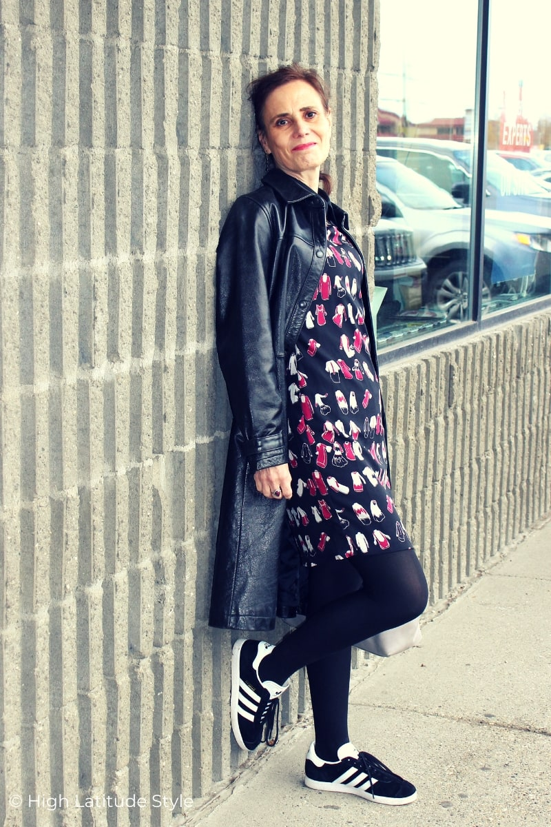 style book author in print dress, black leather coat, Adidas sneakers, tights