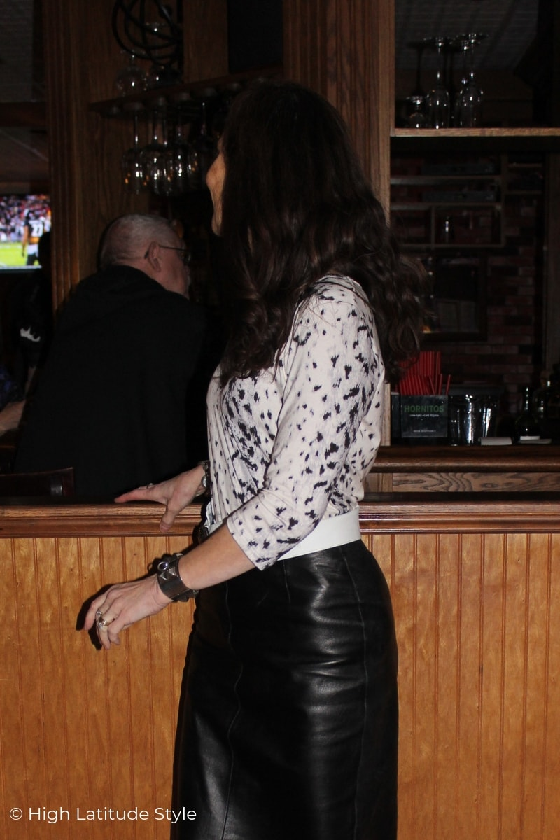 over 50 years old woman with spotted top standing in a bar