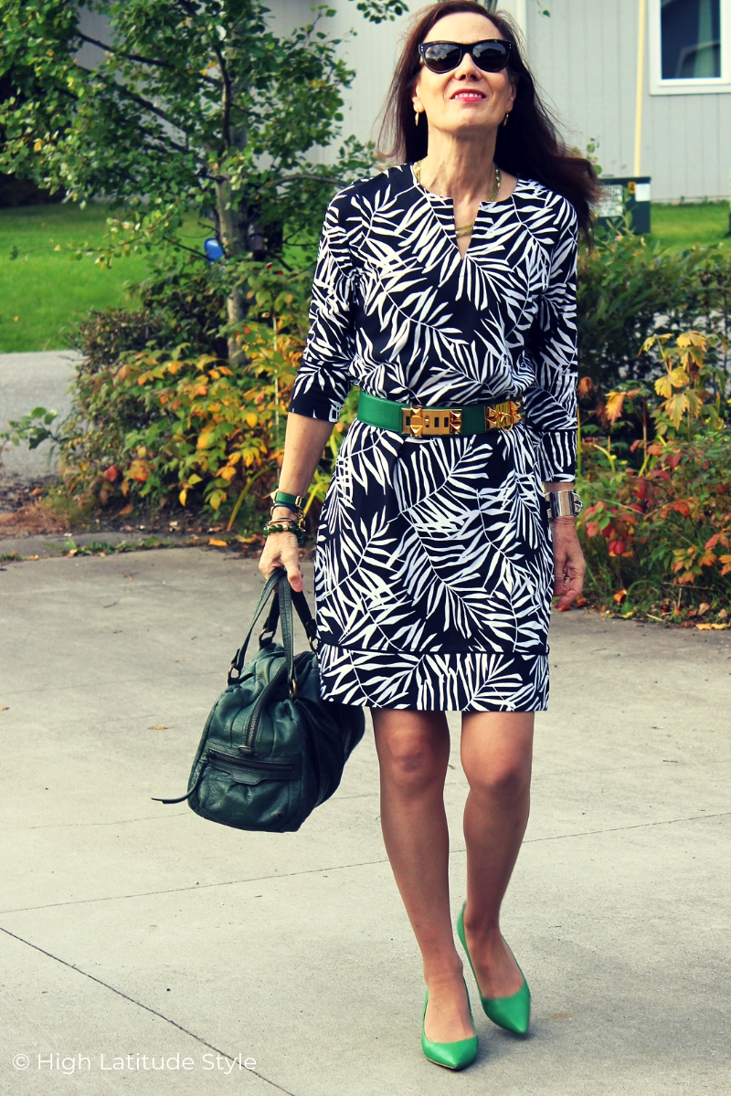 fashion blogger in black dress with white leaf print and green accessories