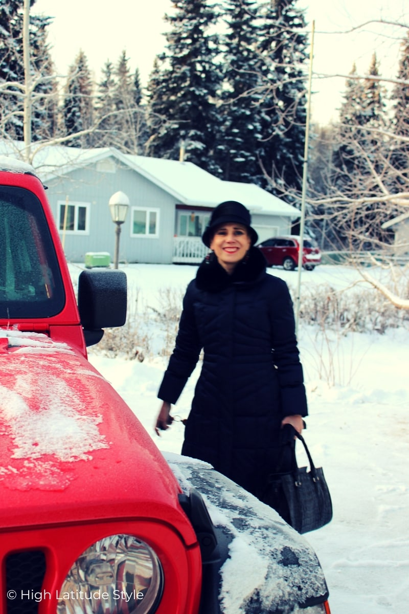 Alaskan woman in downcoat in front of snowed-in Wrangler