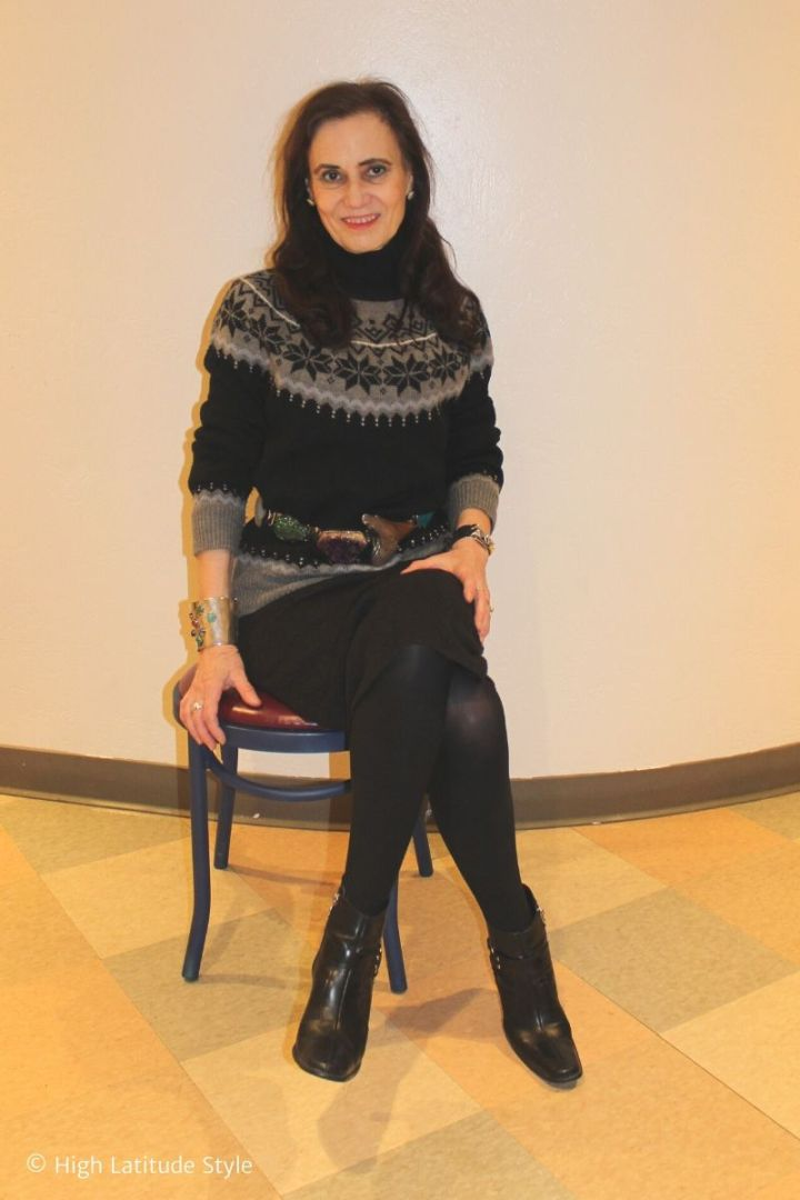 style book author sitting on a chair in cable knit skirt, Fair Isle sweater accessories, tights