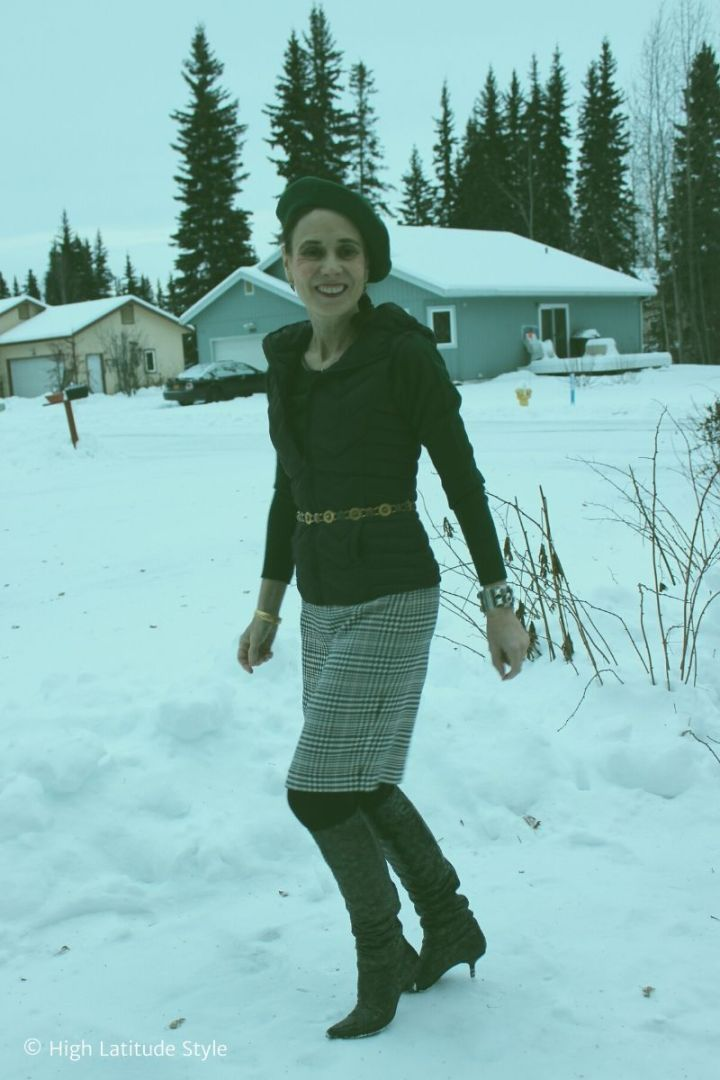 over 50 years old woman walking thru the snow in huntergreen sweater and black and white skirt