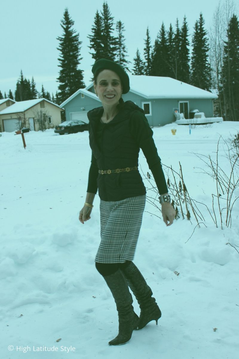over 50 years old woman walking thru the snow in hunter green sweater and black and white skirt
