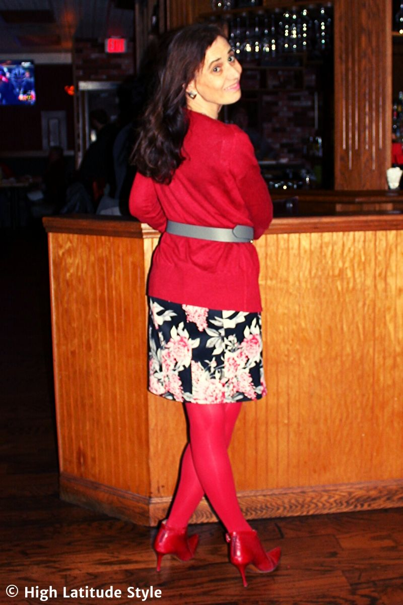style blogger in floral bottom, red tights, booties and top with triangle ear jewelry