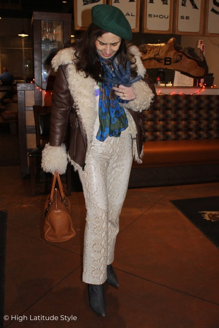 stylist wearing reptile-print pants, denim booties, a motorcycle jacket, gloves and a beret