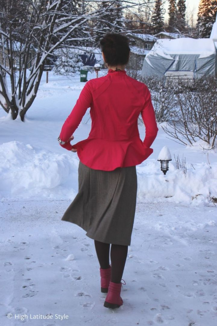 woman in pink top, brown glen check midi skirt, tights and pink shoews walking in snow