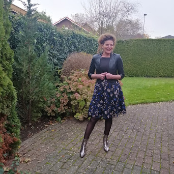 Nancy of Nancy's Fashion Style in a black floral skirt, black top and leather bolero with sheer black tights and metalic booties