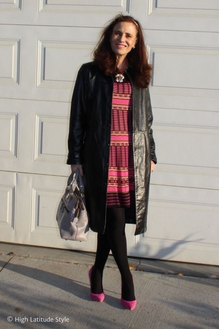 stylist in patterned dress, pink pumps, black tights and leather coat with shark gray bag