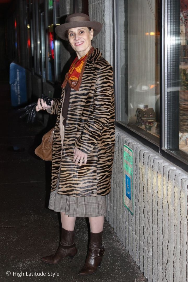 stylist with taupe hat in zebra print pony hair coat, glenchekc skirt, sweater, scarf, gloves, bag, pantyhose and booties