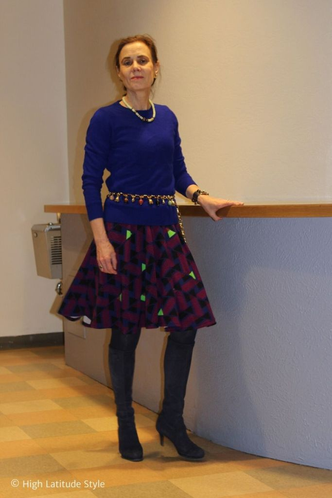 style book author in A-line skirt, belt, top, tights and boots office look