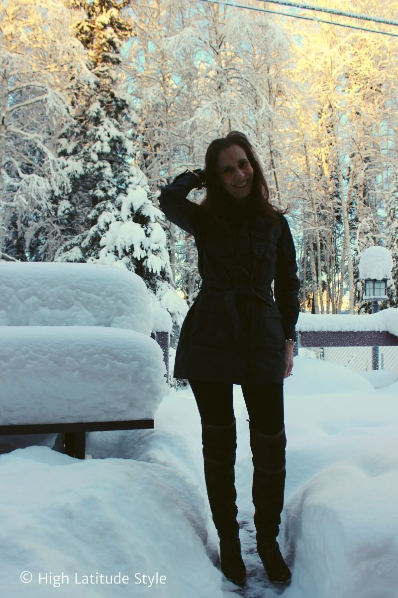 blogger in utility jacket, pants, otk-boots standing in a winter landscape