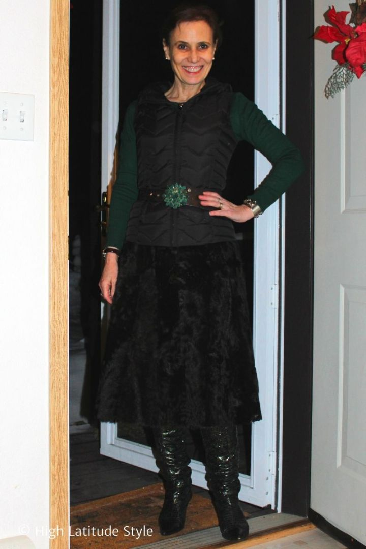 stylist donning a fur a-line skirt, down vest, statement belt buckle and sweater winter look