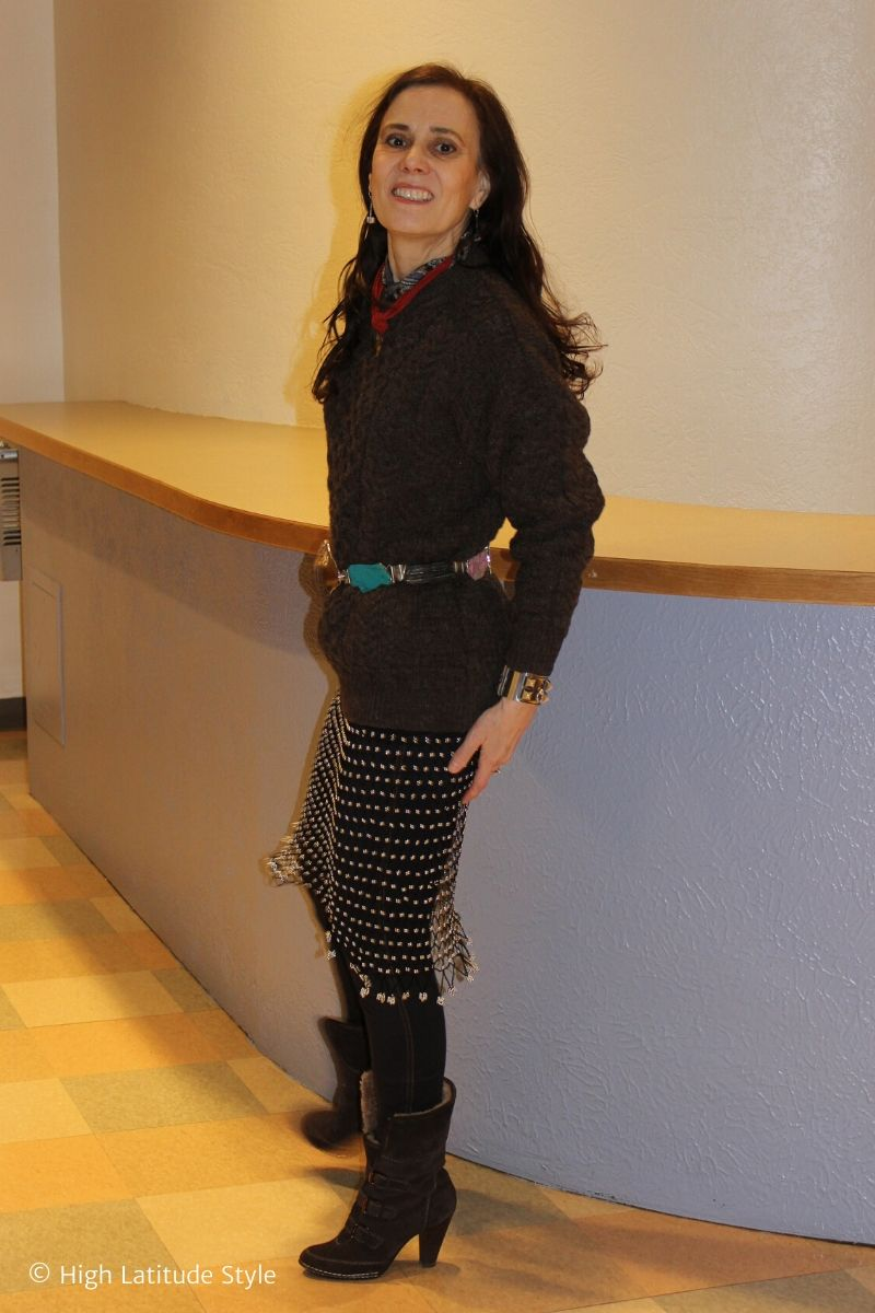 over 50 years old stylist in mesh dress, cable knit sweater, statement belt, shealing booties