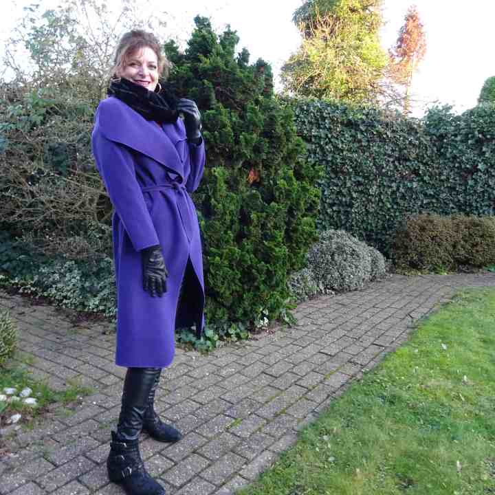 Nancy Baten in a purple midi coat with black collar, gloves, leather trousers and edgy booties