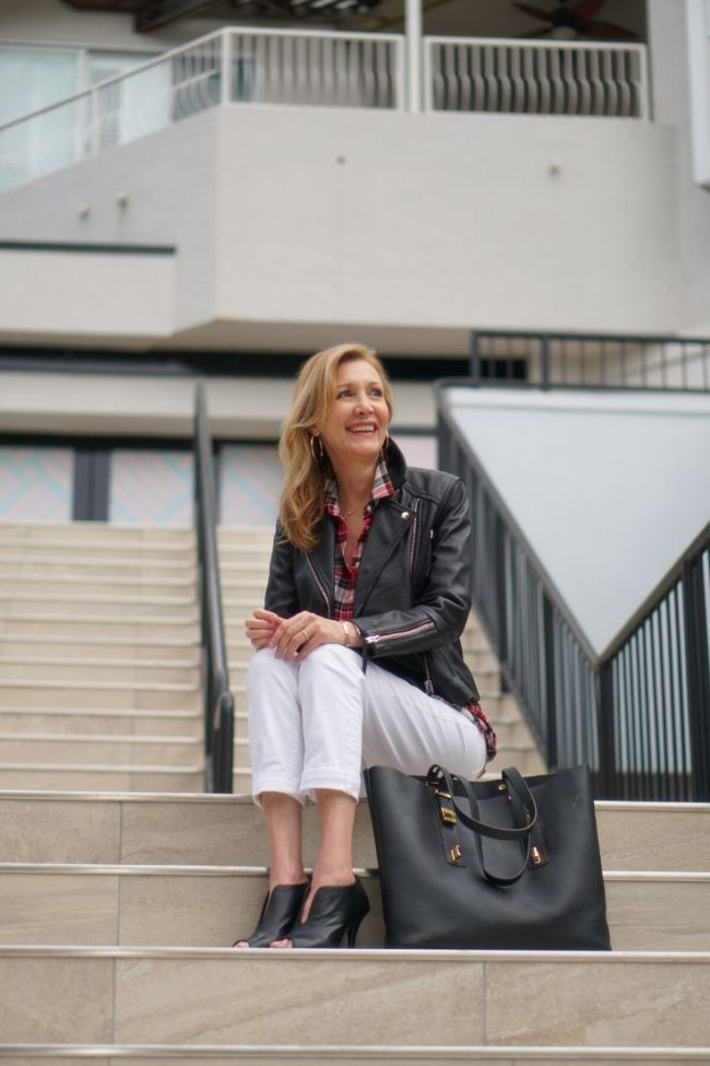 Nina Bandoni of Sharing a Journey illustrates chic cozy looks in Florida in white pants, leather jacket and open toe-booties