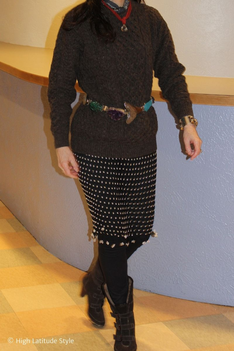 stylist in mesh dress, skinny jeans, cable knit sweater, pendant necklace and statement belt