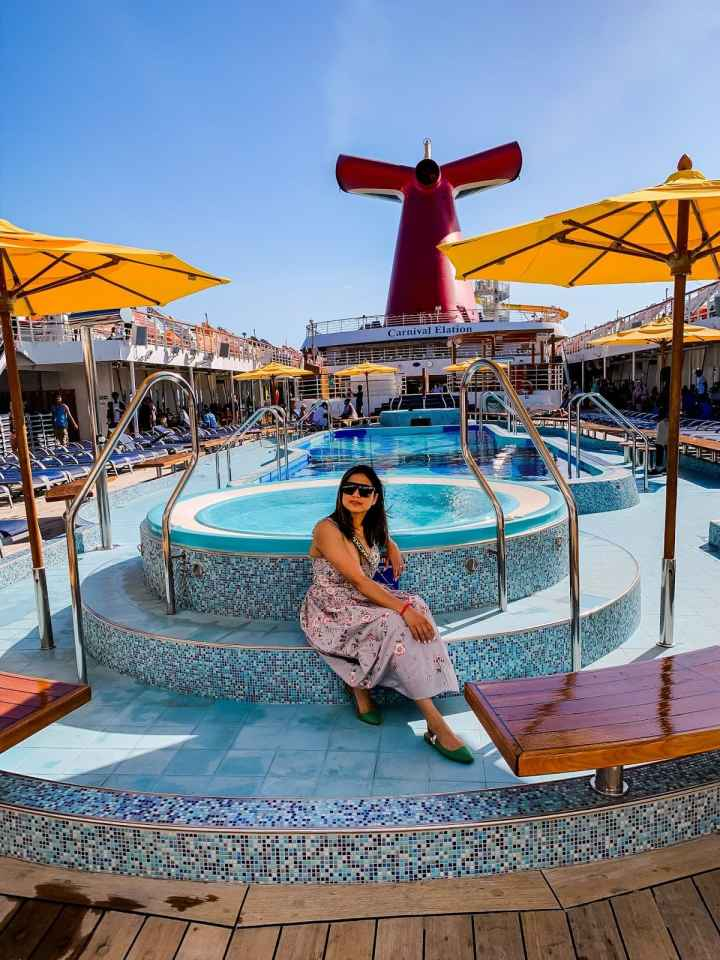 Top of the World OOTD Readers' Fav Saumya of Myriad Musings sitting at a pool on a cruiseship
