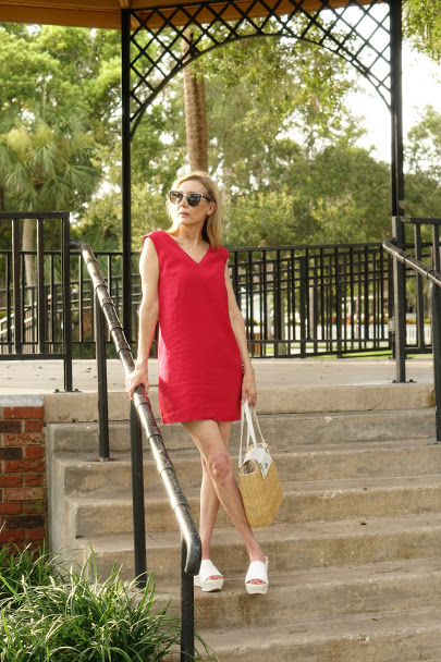 Nina in a carmine mini dress and white plateau shoes with straw and leather bag