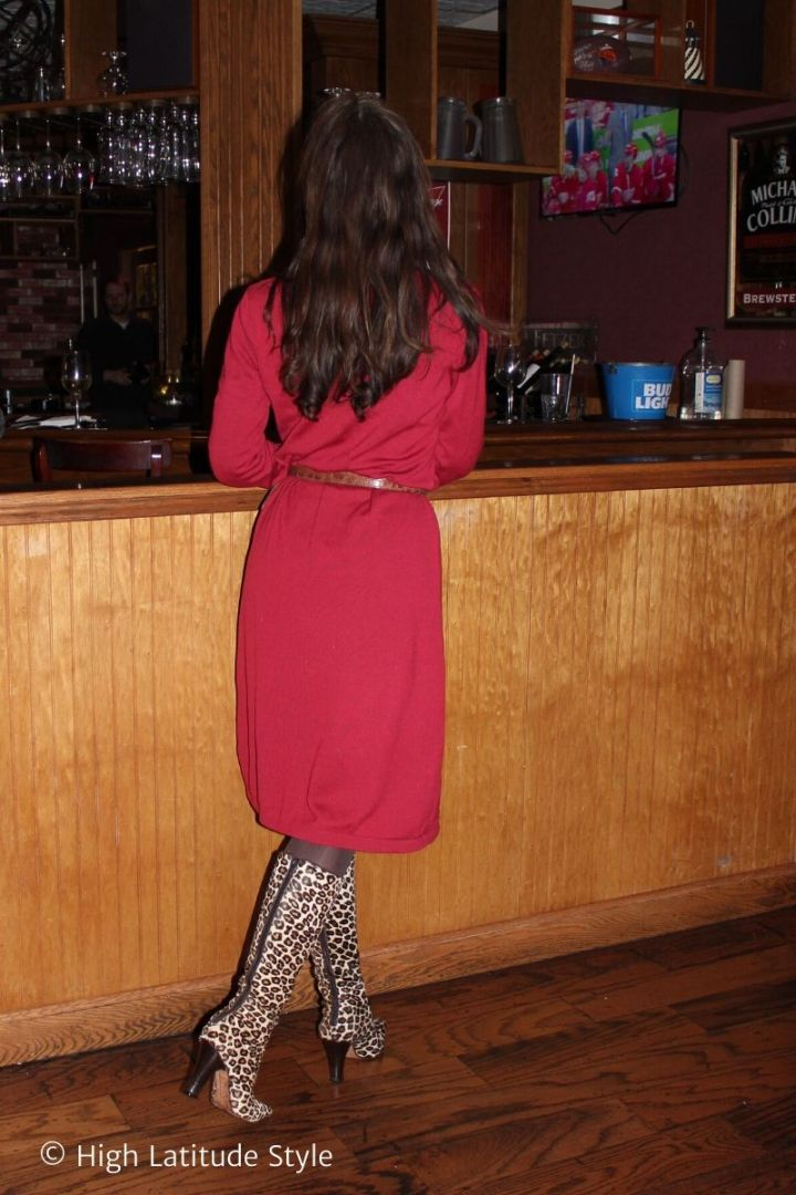 fashion blogger with long curls, knitdress, tall boots