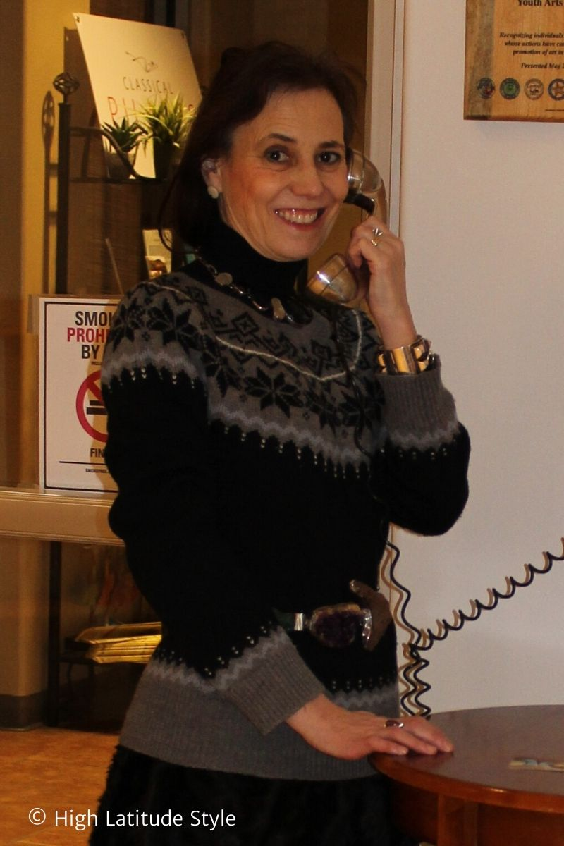 stylist in gray black Fair Isles sweater, statement jewelry and belt