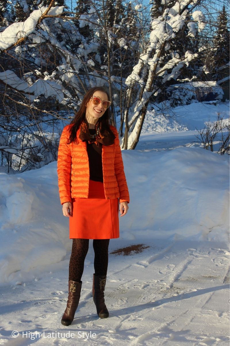 style book author in orange skirt and puffer blazer, brown tights, sweater and orange brown printed scarf