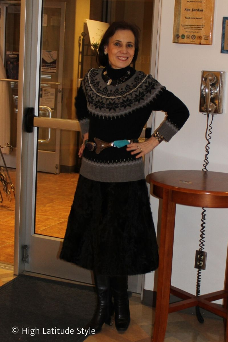 style book author in winter outfit with fur skirt, sweater, colorful accessories