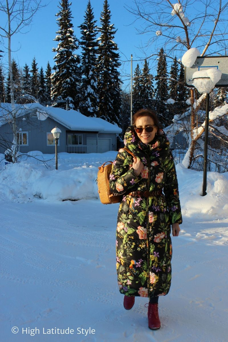 Alaskan woman doing street style with long down coat, sunnies, booties, vegan bag and wood belt