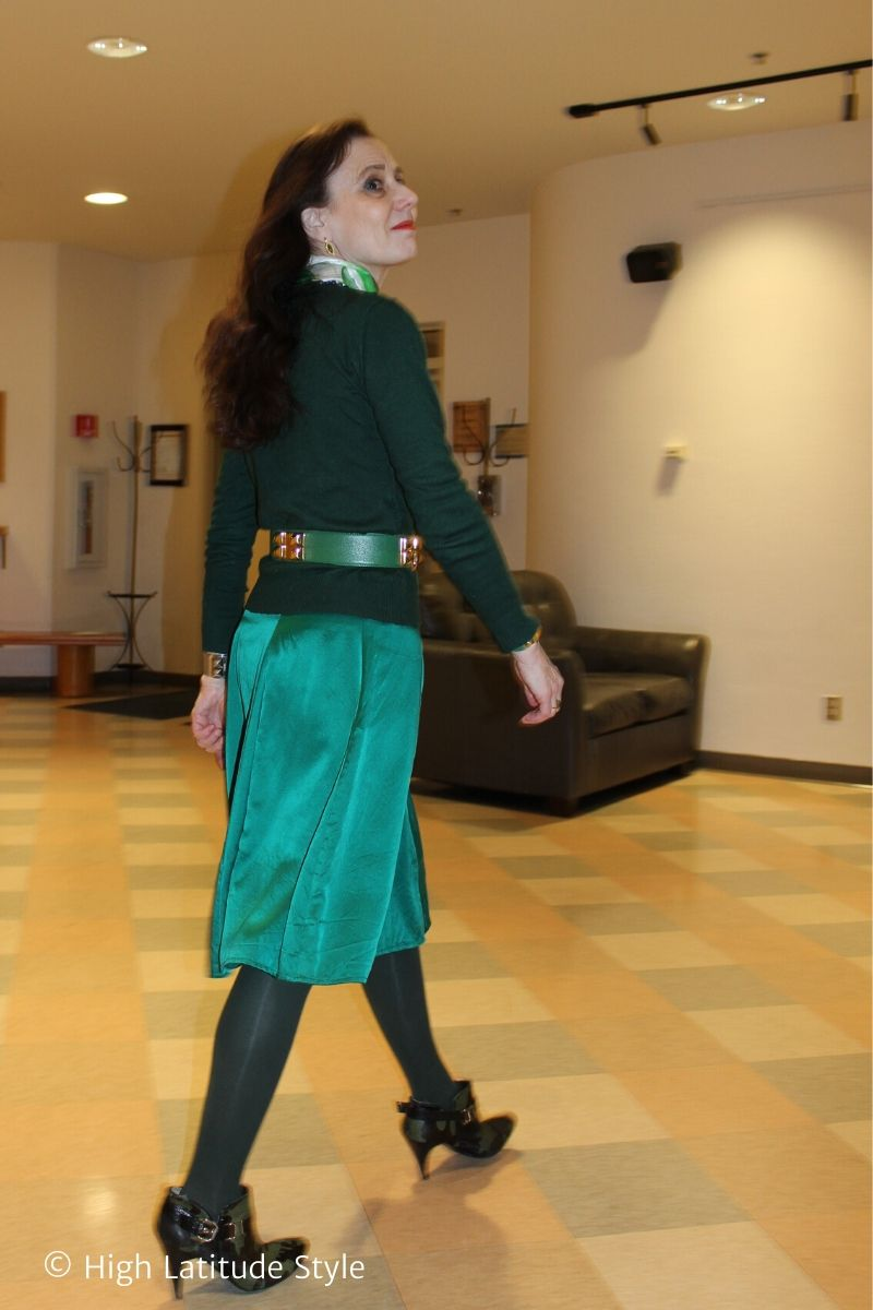 older woman in monochromatic work style of silk skirt, cashmere sweater, tights and shoes walking in a hall