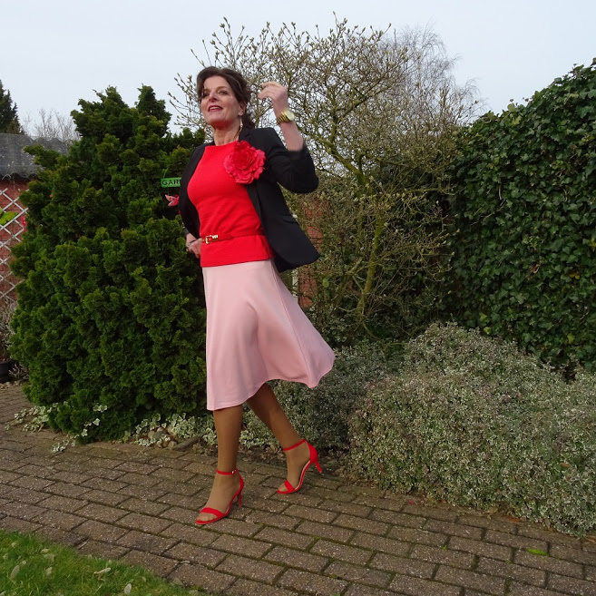 Nancy Baten of Nancy's Fashion Style in pink skirt, sandals, black blazer with rose coral belt and top