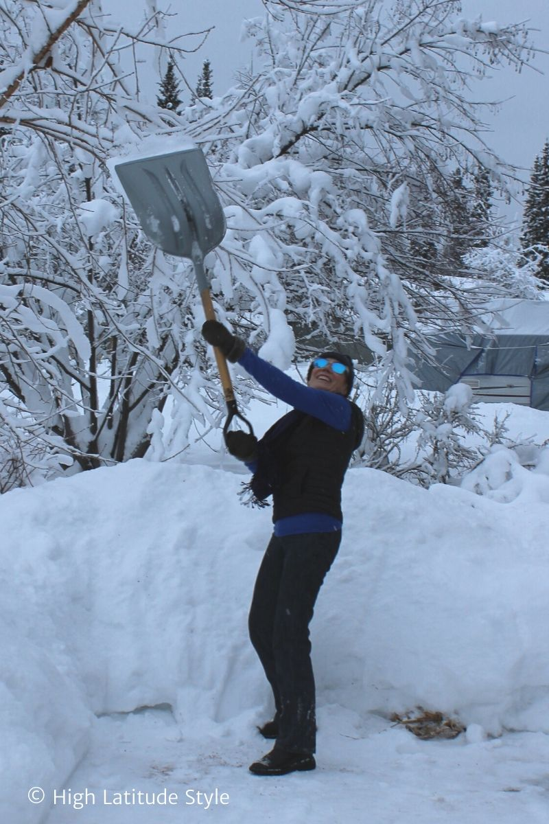 Alaskan woman shoveling snow in scarf, sweater, shearlin booties and mittens, pompom hat down vest and sunglasses