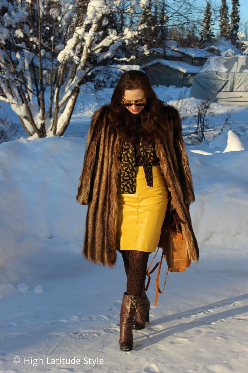 Nicole in thrifted striped coat, leopard scarf and tights walking in a snow-covered neighborhood