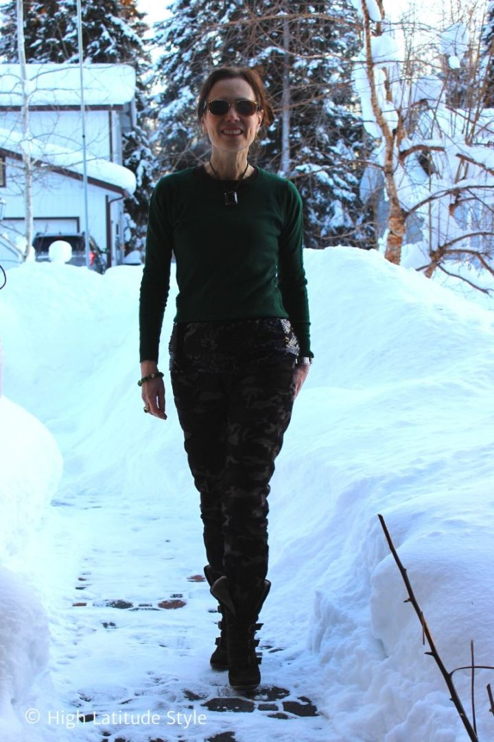 style blogger wearing an eclectic look with camouflage pants, sequin top, sweater, booties, statement necklace
