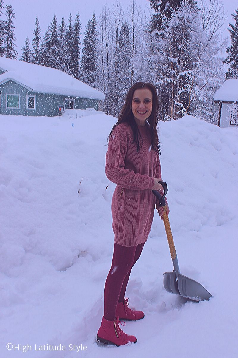 Alaskan woman in pink attire standing in a snow storm