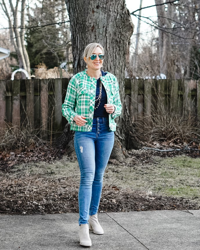 Top of the World Style winner Jill in distressed jeans, sweater, white booties, green plaid jacket, mirrored sunglasses