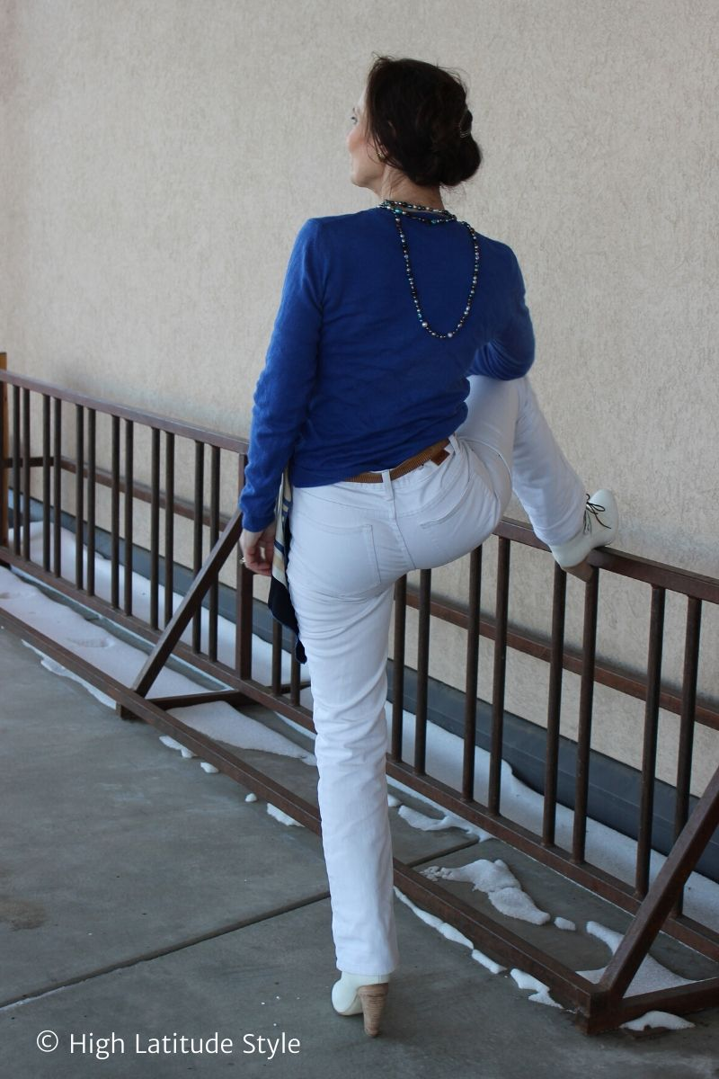 stylist in white denim boyfriend pants, blue sweater and pearls