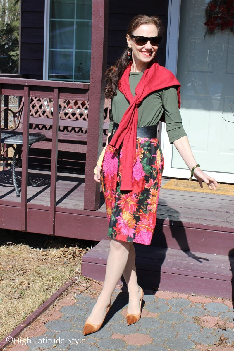 Nicole in flower print around the knee skirt, olive Tee, red cardigan knotted around the neck, tan heels
