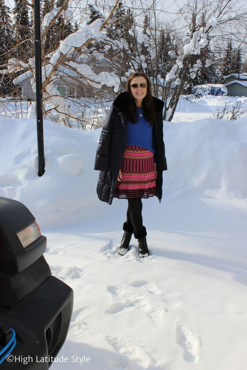 over 50 years old woman in cute pink skirt, wedge boots, blue coat and sweater with pendant necklace