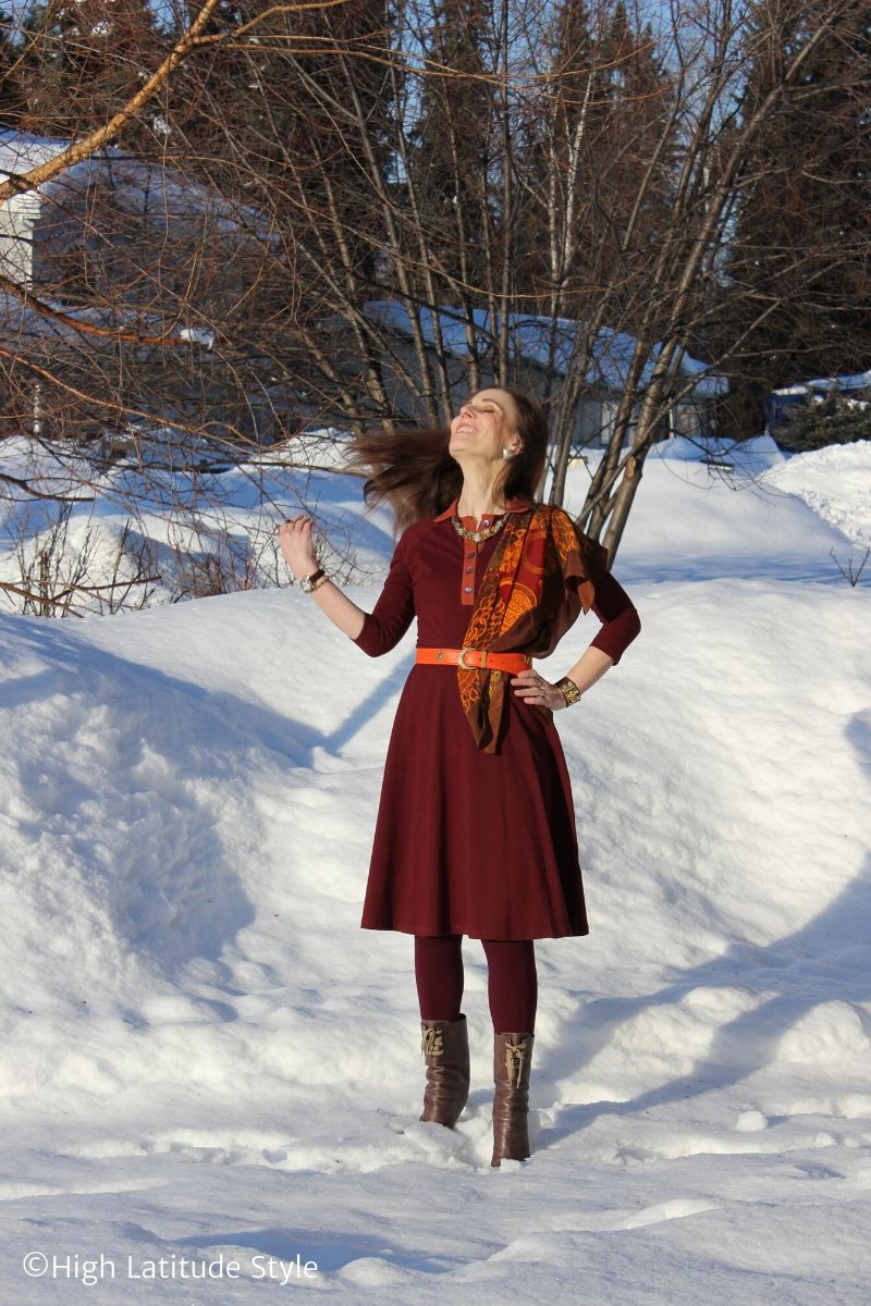 style book author in orange-burgundy work dress, accessorized with scarf, belt, necklace, cuff