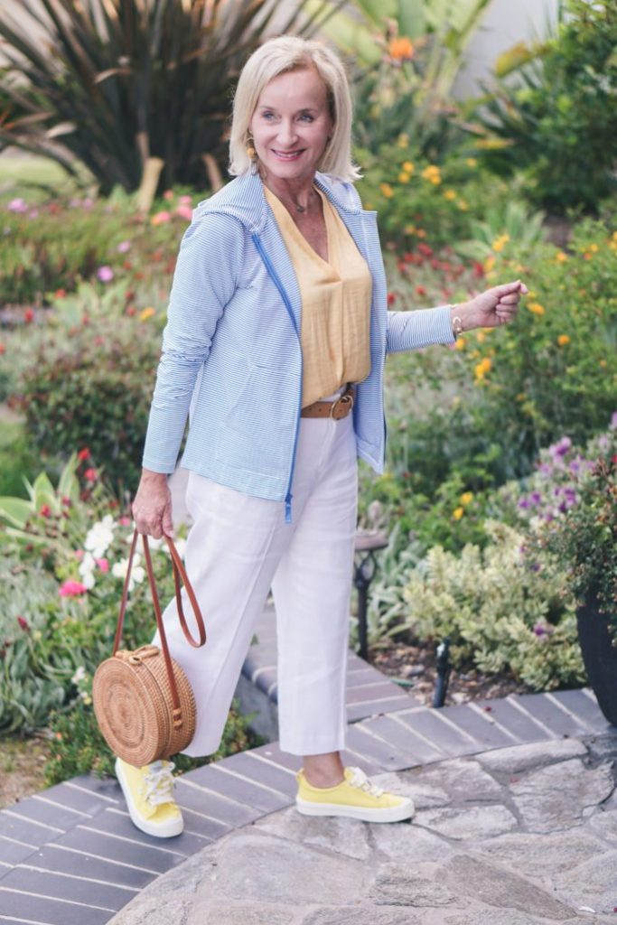 Darlene in white pants, yellow sneakers and blouse, baby blue jacket