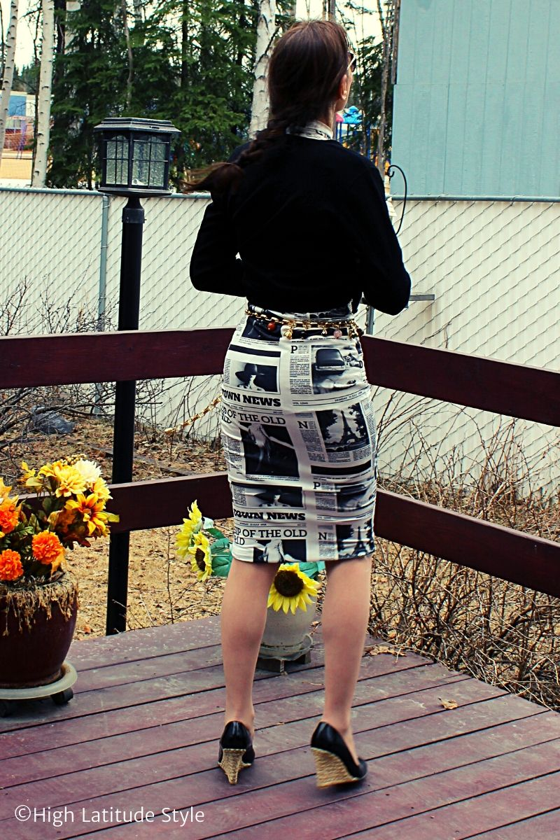 back view of black and white print dress with black jacket and wedge heels
